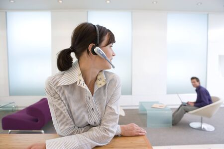 handsfree device: Businesswoman with headset, colleague in background