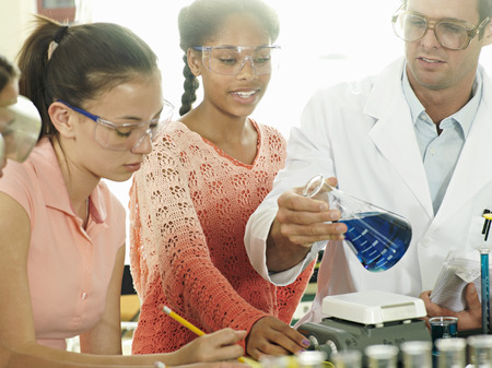 Teenage girls (15-17) doing science experiment at desk in classroom, teacher assisting, smiling