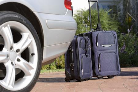 차도에 주차 된 차 옆에 바퀴에 두 개의 가방 (표면 레벨)