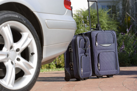 Two suitcases on wheels beside parked car on driveway (surface level) Imagens