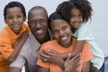 two generation family: Two generation family smiling, boy (7-9) and mother wearing orange tops, portrait