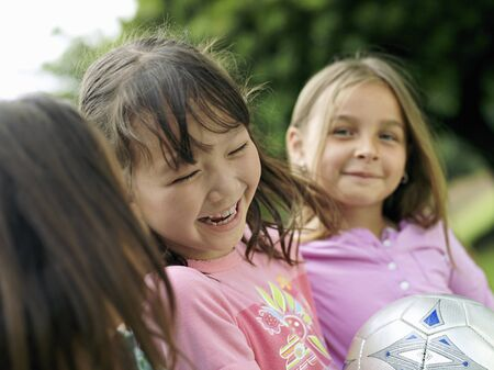 differential focus: Three girls (7-9) laughing, one girl with soccer ball, close-up, portrait (differential focus) LANG_EVOIMAGES