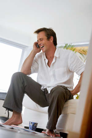 tilt view: Man using mobile phone, laughing, sitting on sofa at home, side view, surface level (tilt) LANG_EVOIMAGES