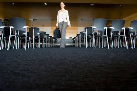 lecture hall: Businesswoman with briefcase leaving empty lecture hall