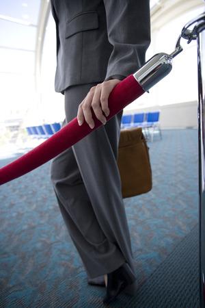 velvet rope: Businesswoman next to velvet rope in airport