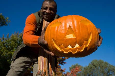 jack'o'lantern: Senior man holding jack-o-lantern LANG_EVOIMAGES