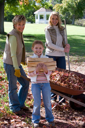 yard work: Multi-generational family doing yard work in autumn