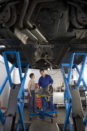 underneath: Mechanic with part in conversation with woman by elevated car, low angle view