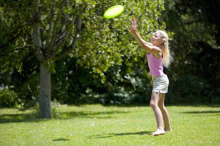 flying disc: Girl (8-10) catching flying disc outdoors