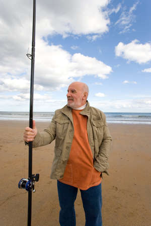 only one senior adult man: Senior man with fishing rod on beach