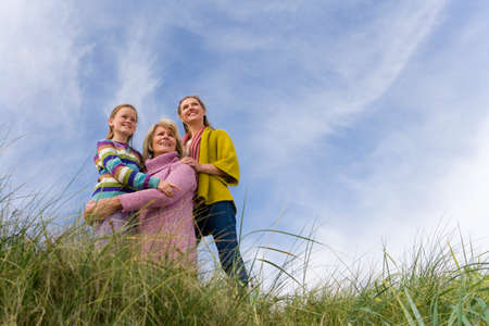 three generations of women: Family of three generations of women on sand dune, smiling, low angle view
