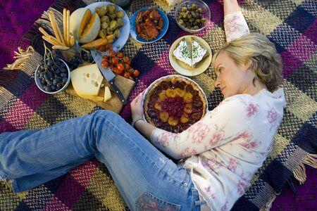 picnic blanket: Mujer en manta de picnic tarta abrazo, visi�n elevada, fotograma completo