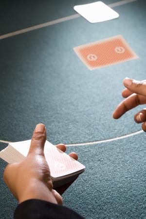 Croupier dealing cards, close-up of hands