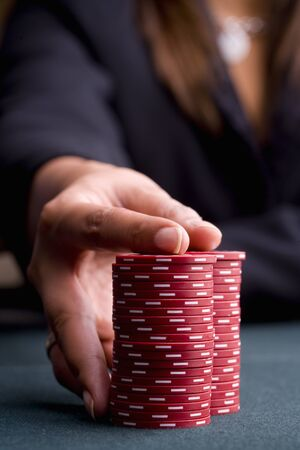 high stakes: Woman with hand on pile of gambling chips, close-up of hand
