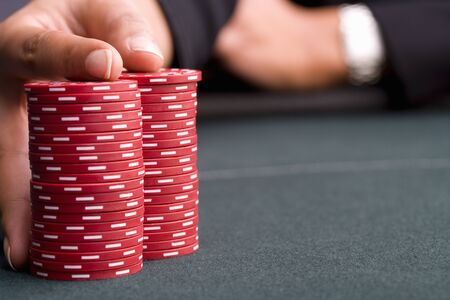 high stakes: Woman with hand on pile of gambling chips, close-up