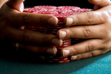 hope indoors luck: Woman with hands around piles of gambling chips on table, close-up of hands