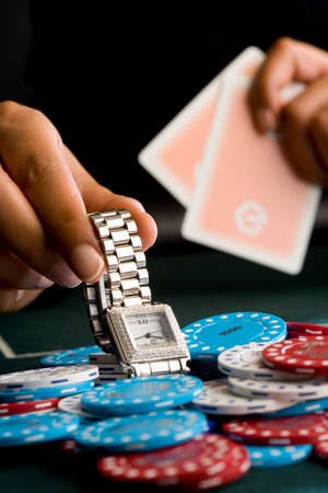 high stakes: Woman placing watch on pile of gambling chips on table, close-up LANG_EVOIMAGES