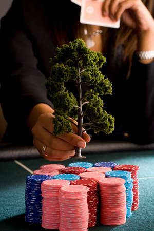 high stakes: Woman placing model tree on pile of gambling chips on table, mid section LANG_EVOIMAGES