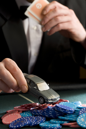 by placing: Man placing model car on pile of gambling chips on table, mid section LANG_EVOIMAGES