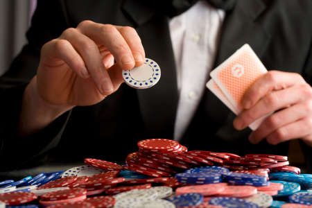 gambling chip: Man placing gambling chip on pile of chips on table, mid section