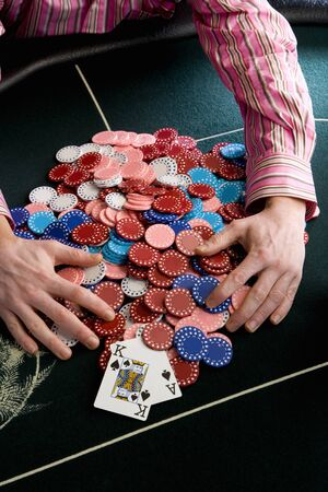 Man collecting pile of gambling chips on table, mid section, elevated view