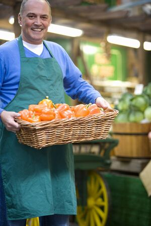 grocer: Green grocer with basket of peppers, smiling, portrait LANG_EVOIMAGES