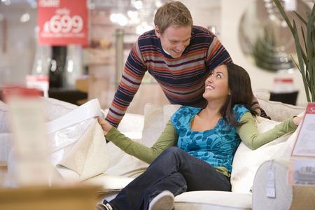 젊은 부부 쇼핑, 남자는 소파에 여자 미소