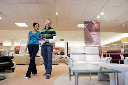 Young couple in furniture shop, smiling, portrait, low angle view
