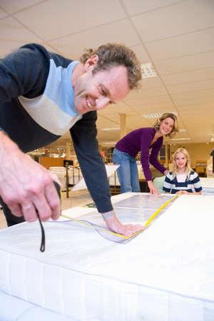 width: Man measuring bed in furniture shop, family in background, smiling LANG_EVOIMAGES