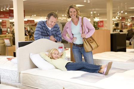 Familie von drei im Möbelhaus, Tochter (6-8) auf dem Bett, Lächeln, Portrait