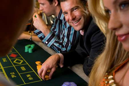 roulette table: Man gambling at roulette table, smiling, portrait