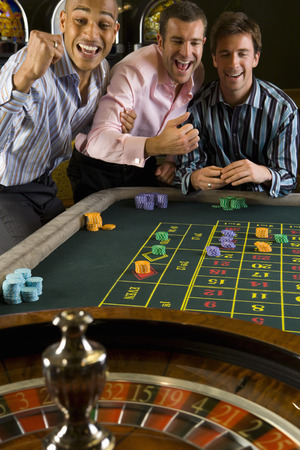 roulette wheel: Young man and friends gambling at roulette table in casino, smiling