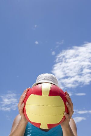 one mid adult woman only: Man obscuring face with ball outdoors, low angle view LANG_EVOIMAGES