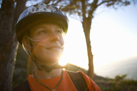 away from it all: Young woman in bicycle helmet, smiling, close-up (lens flare)
