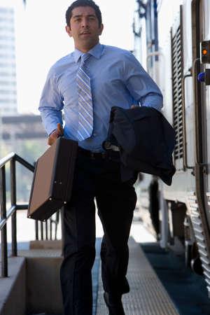 businessman running: Businessman running to catch train LANG_EVOIMAGES