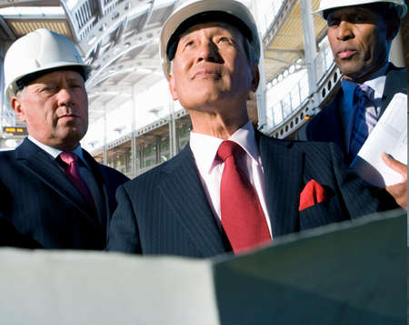 toiling: Businessmen inspecting construction site