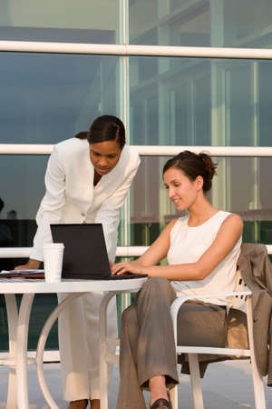 toiling: Businesswomen using laptop at outdoor cafe LANG_EVOIMAGES