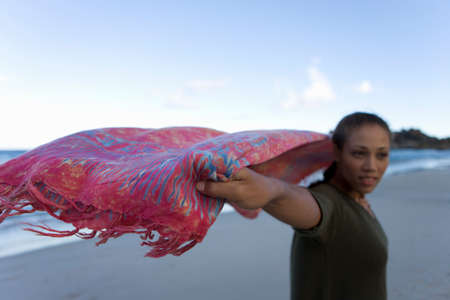 differential: Woman with sarong flying in wind on beach, smiling (differential focus)