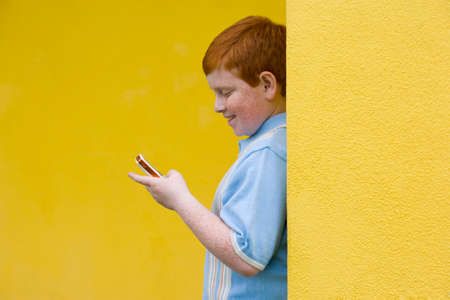 Boy (9-11) with mobile phone, smiling, side view Stock Photo