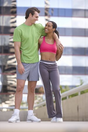 adoring: Young couple in exercise clothes, smiling at each other