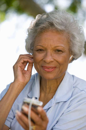 mp3 player: Senior woman with MP3 player, smiling, portrait