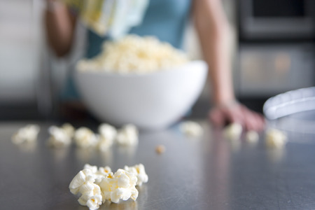popcorn kernel: Woman with popcorn in kitchen