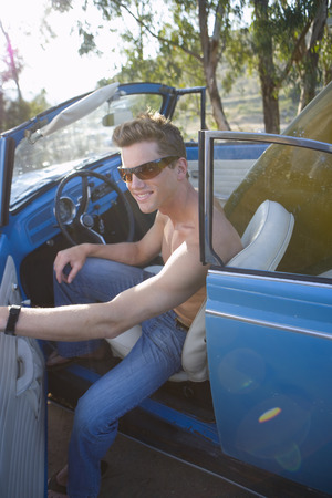 bare chested: Bare chested man in convertible car, smiling, portrait LANG_EVOIMAGES
