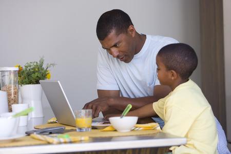 노트북 컴퓨터에서 아버지와 아들 (7-9) 스톡 콘텐츠