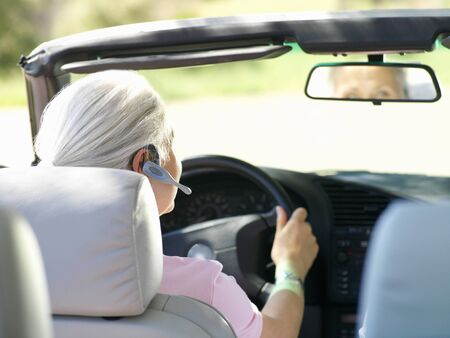 handsfree device: Woman with hands-free device in car, rear view