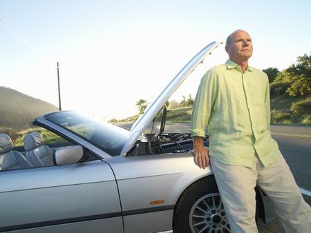 roadside stand: Senior man by broken down car on roadside LANG_EVOIMAGES