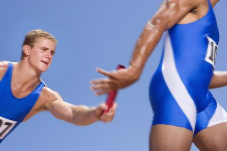 relay race: Young male athletes passing relay race baton LANG_EVOIMAGES