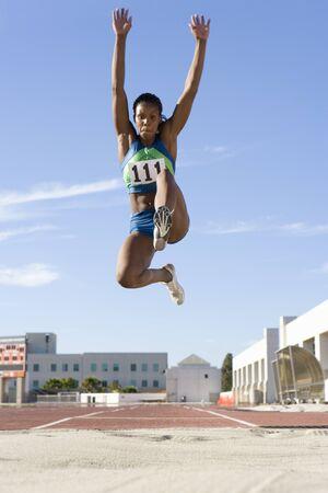 salto largo: Femenina africana atleta el aire durante el salto de longitud