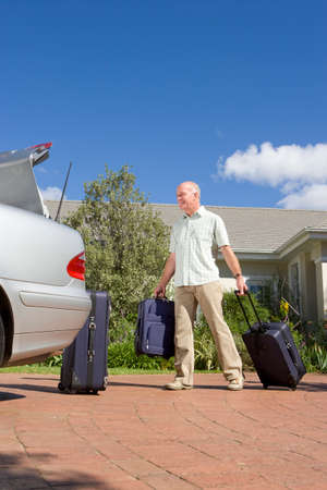 car trunk: Man loading suitcases into car trunk LANG_EVOIMAGES