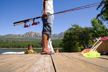 Fishing pole: Man holding fishing pole on dock LANG_EVOIMAGES